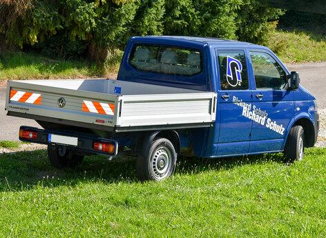 Pritschenwagen mit Beschriftung und Warnmakierung